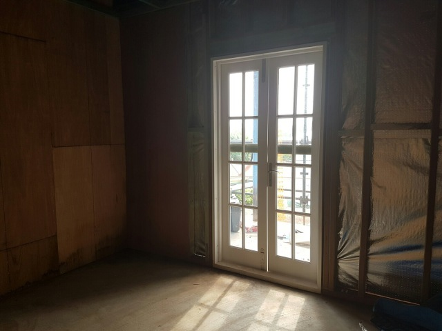 New multi-lite French doors in one of the downstairs bedrooms, leading out to the patio
